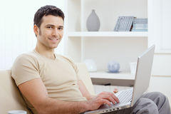 Happy man using computer. Happy young man in t-shirt sitting on sofa at home, working on laptop computer, smiling stock images