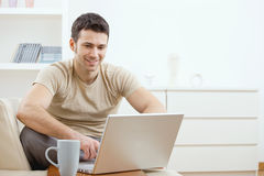 Happy man using computer. Happy young man in t-shirt sitting on sofa at home, working on laptop computer, smiling Royalty Free Stock Photos