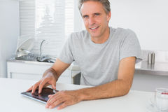Happy man using digital tablet in kitchen Stock Image