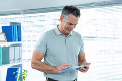 Happy man using digital tablet. In office in office Royalty Free Stock Image
