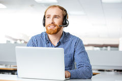 Happy man using headset and laptop in office. Happy handsome young man using headset and laptop in office Stock Images