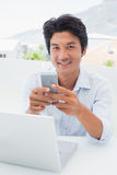 Happy man using his laptop and texting on phone Stock Photography