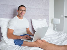 Happy man using laptop on bed Stock Photo
