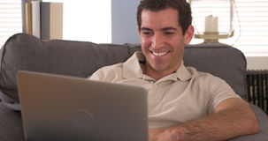 Happy man using laptop on couch Stock Image