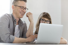 Happy man using laptop with daughter at home Stock Photo