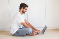 Happy man using laptop on floor Royalty Free Stock Photo