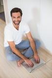 Happy man using laptop on floor Stock Photography