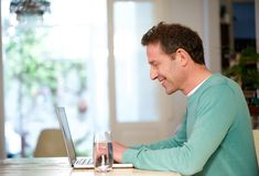Happy man using laptop at home Royalty Free Stock Photography