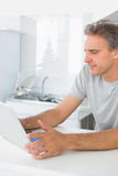 Happy man using laptop in kitchen Royalty Free Stock Photos
