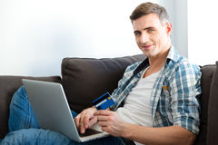 Happy man using laptop and making purchases with credit card Royalty Free Stock Image