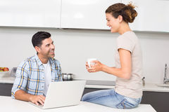 Happy man using laptop while partner sits with a coffee Stock Photo