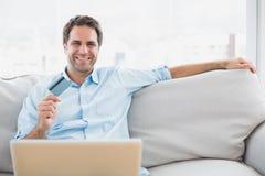 Happy man using laptop sitting on sofa shopping online Stock Image