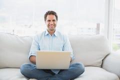 Happy man using laptop smiling at camera sitting on sofa Stock Images