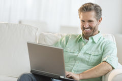 Happy Man Using Laptop On Sofa Royalty Free Stock Images