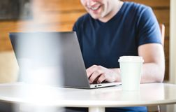 Happy man using laptop with take away coffee cup on table. royalty free stock images