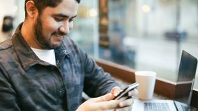 Happy man using mobile phone in cafe. Sending selfie to friends. Video footage. Latin hispanic brunette appearance. Happy man using mobile phone in cafe. Sending stock footage