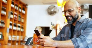 Happy man using mobile phone while having beer at counter 4k. Happy man using mobile phone while having beer at counter in bar 4k stock footage