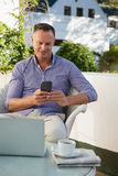 Happy man using mobile phone while sitting in cafe Royalty Free Stock Photos