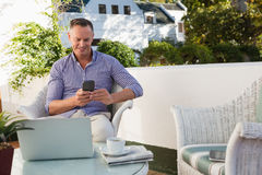 Happy man using mobile phone while sitting at cafe Royalty Free Stock Photos