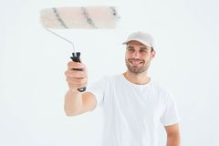 Happy man using paint roller. On white background Stock Photo