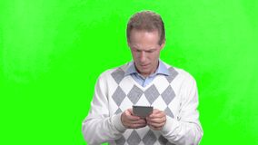 Happy man using smartphone, green screen. Positive mature man playing game on his smartphone standing on chroma key background stock video footage