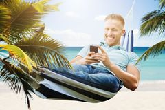 Happy Man Using Smartphone In Hammock royalty free stock images