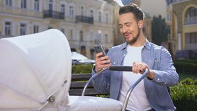 Happy man using smartphone near baby carriage, surprised by easy mobile app. Stock footage stock footage
