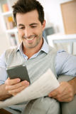 Happy man using smartphone and newspaper together Royalty Free Stock Photos