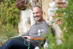 Happy man using tablet from bench in garden Royalty Free Stock Photo