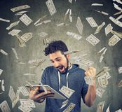 Successful man with tablet under money rain. Happy man using a tablet computer and posing with triumph under flying dollar bills Royalty Free Stock Photography
