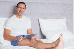 Happy man using tablet pc on bed Royalty Free Stock Photography
