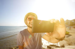 Happy man on vacation taking a selfie at the beach Royalty Free Stock Photos