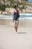 Happy man on vacation walking on isolated beach Stock Image