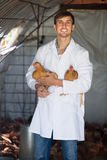 Happy man veterinarian in white coat. Holding brown chickens in hands on farm Stock Photo