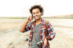 Happy man with vintage photo camera talking on mobile phone. Happy african young man with vintage photo camera talking on mobile phone outdoors Royalty Free Stock Photos