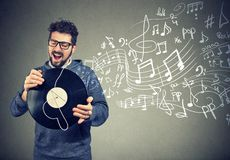 Happy man with vinyl record disc listening to music. Happy casual man with vinyl record disc listening to music singing Stock Photos