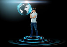 Happy man in virtual reality headset or 3d glasses. 3d technology, augmented reality, gaming, cyberspace and people concept - happy young man with virtual Stock Photo