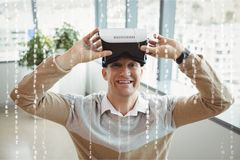 Happy man with VR headset standing behind interfaces. Digital composite of Happy man with VR headset standing behind interfaces Royalty Free Stock Photography