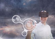 Happy man in VR headset touching interface against purple sky with clouds and interface. Digital composite of Happy man in VR headset touching interface against Stock Photos