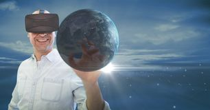 Happy man in VR touching 3D planet with flares against blue sky Stock Photo