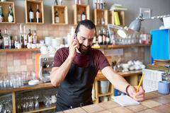 Happy man or waiter at bar calling on smartphone. Small business, communication, people and service concept - happy man or waiter in apron calling on smartphone Stock Photos