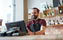 Happy man or waiter at bar cashbox. Small business, people and service concept - happy man or waiter in apron at counter with cashbox working at bar or coffee royalty free stock photography