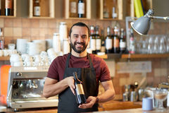 Happy man or waiter with bottle of red wine at bar Royalty Free Stock Photo