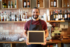 Happy man or waiter with chalkboard banner at bar Stock Photo