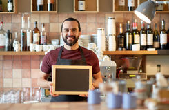 Happy man or waiter with chalkboard banner at bar Stock Photos