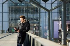Happy man waiting at station and looking at mobile phone Stock Images