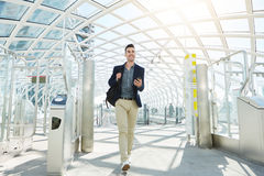 Happy man walking by automated turnstile with phone Royalty Free Stock Image