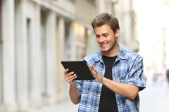 Happy man walking browsing tablet online content. In the street royalty free stock image
