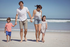 Happy man walking with his family while holding hands at beach Royalty Free Stock Photo