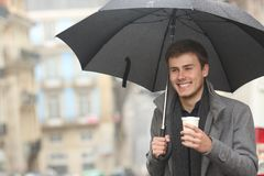 Happy man walking holding a takeaway drink in winter. Under the rain in the street royalty free stock images